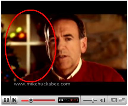 Huckabee in front of subliminal-cross bookshelf